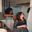 Fellow roommate Ama doing Mandavi's hair on her birthday