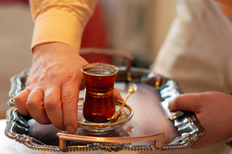 Omar Muhammad serves traditional Iraqi chai tea in a cup brought from his home in Baghdad. Photo by Blake Sobczak